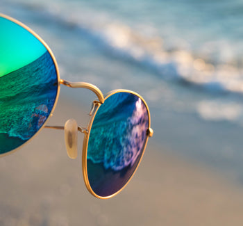 Multicolor mirrored polarized sunglasses with the beach in the background