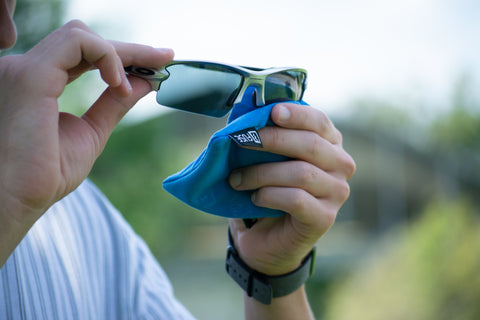 A man holding up his grey sport sunglasses and cleaning them with a Fuse Lenses cloth