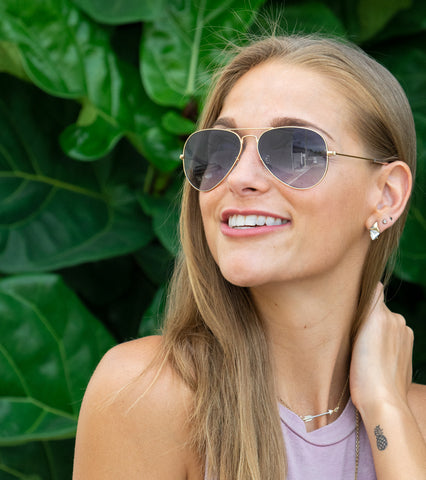 Smiling blonde woman wearing aviator sunglasses with grey lenses in front of greenery