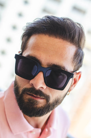 man in red shirt wearing oversized, square black sunglasses
