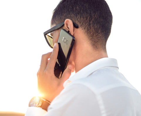 Man in a white shirt talking on his cell phone. Photo by hazardos on unsplash