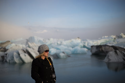 Women looking off into the distance with a beanie and a black jacket while wearing her sunglasses.