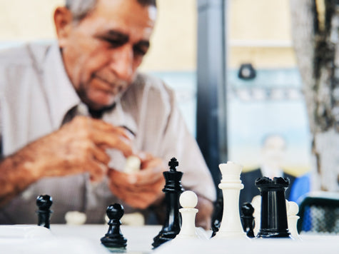 Old cuban man playing chess in Miami, Florida. Photo by Juno Jo on Unsplash