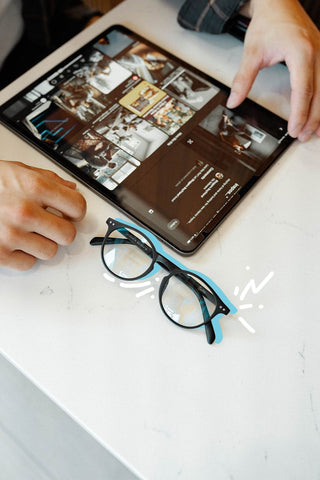 Birds eye view of a desk with blue light glasses and tablet