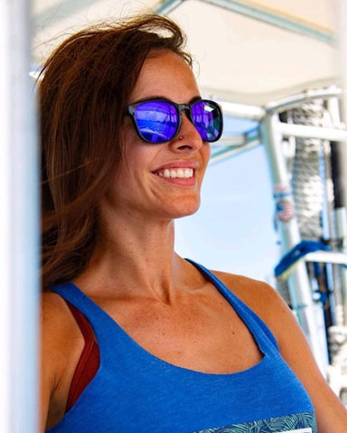 Woman with long brown hair wearing sunglasses with cosmic Fuse Lenses on boat