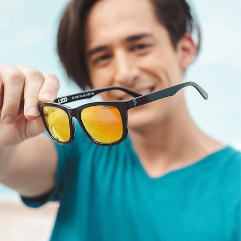 man in blue shirt holding sunglasses with yellow frames
