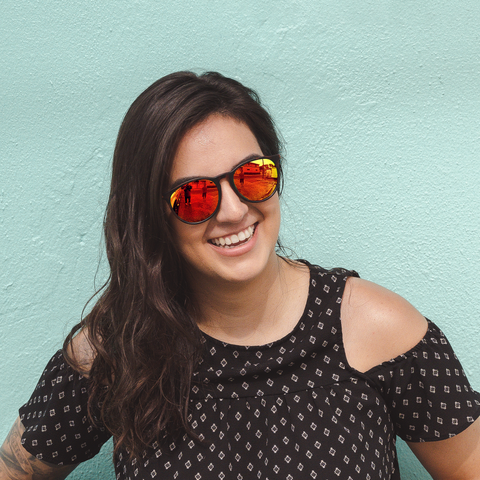 A woman in mirrored lenses laughs with a smile