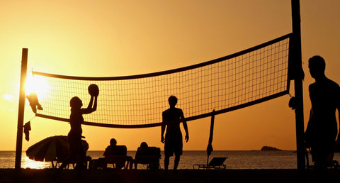 people playing beach volleyball during the sunset
