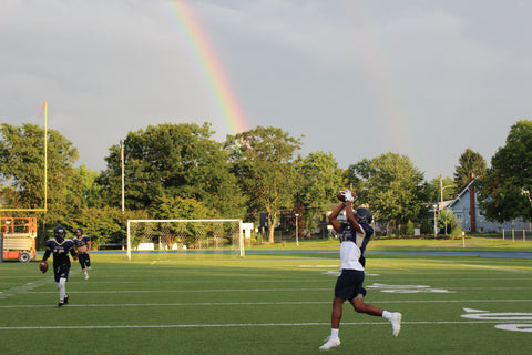 men playing football in on field with rainbow in the background