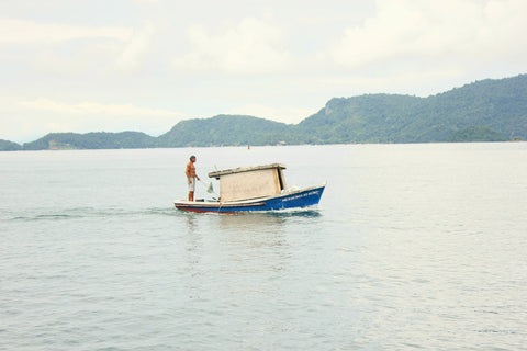 man standing on a boat offshore fishing