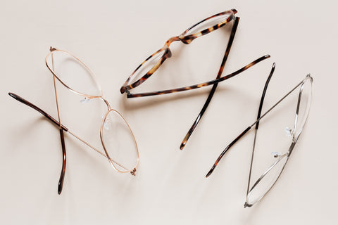 three styles of eyeglasses sitting on a table