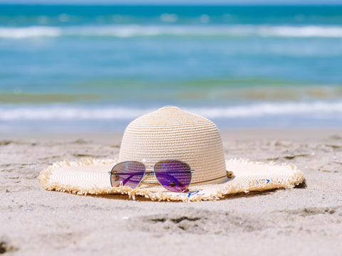 floppy hat with sunglasses on the beach