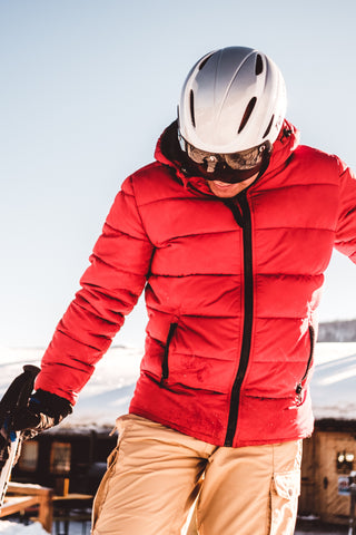 man in red puffy jacket with helmet and sunglasses on snowboarding