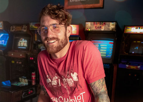 Man smiles in an arcade. His glasses have a light yellow tint