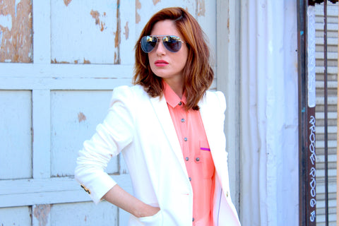 woman in a white blazer and pink shirt wearing aviator style sunglasses in front of a blue wall