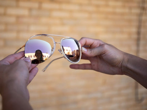 woman holding rose gold pair of aviator sunglasses with one lens popped out