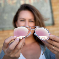 Women holding Ray-Ban Aviator Sunglasses in the lens color Rose Gold
