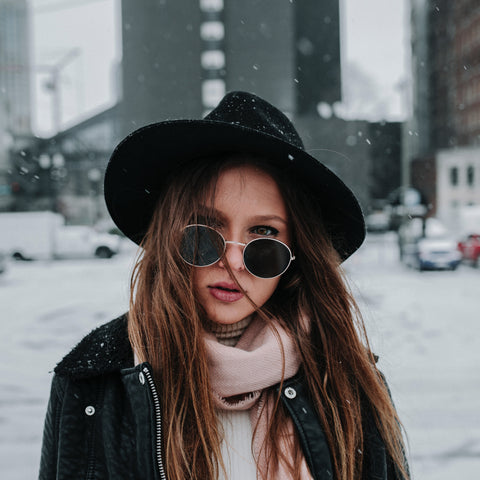 woman in black hat with sunglasses on in the snow