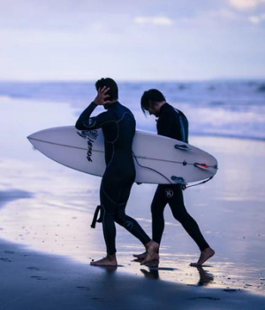 Two surfers walk on a beach at dusk with surfboards in hand