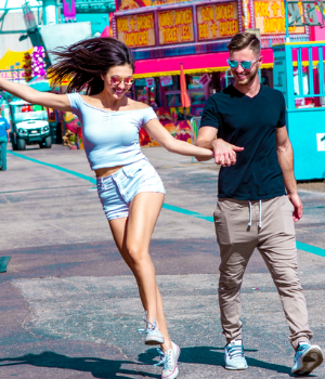 Man and woman skip through carnival with shades on