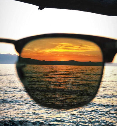 the view of a sunset on the water being looked at through tinted sunglasses