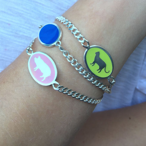 wrist stack of animal id bracelets in multi-colored enamel pink blue and green