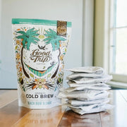 bag of good trip coffee beach bum blondie cold brew sitting on table next to stack of compostable ready-to-steep brew bags