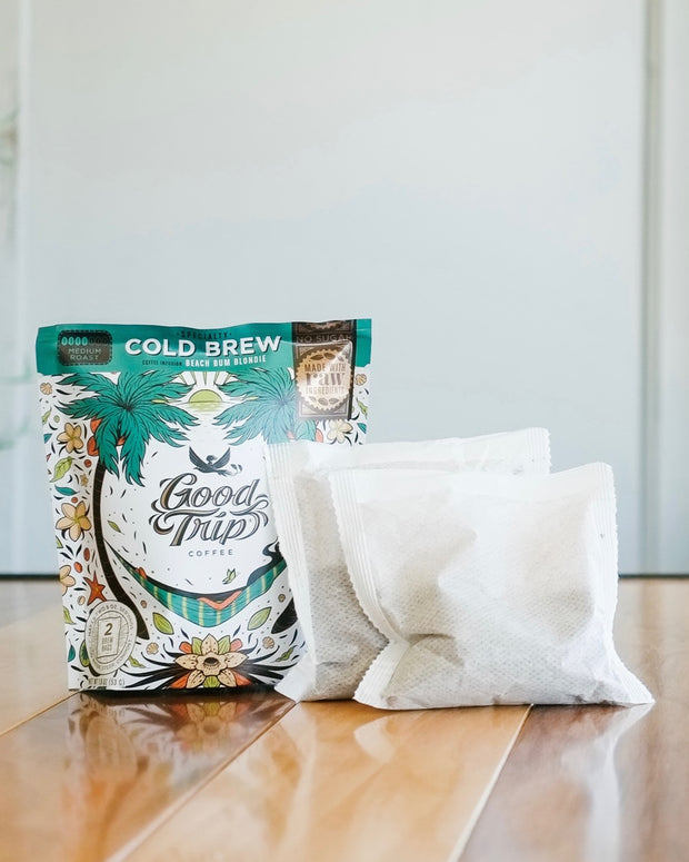 mini bag of good trip coffee beach bum blondie cold brew on wood table next to two compostable brew bags