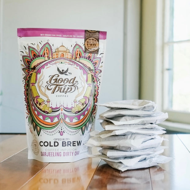 bag of good trip coffee darjeeling dirty chai cold brew sitting on table next to stack of compostable ready-to-steep brew bags
