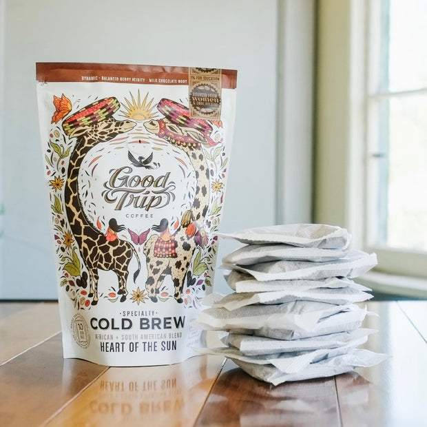 bag of good trip coffee heart of the sun african south american blend cold brew sitting on table next to stack of compostable ready-to-steep brew bags