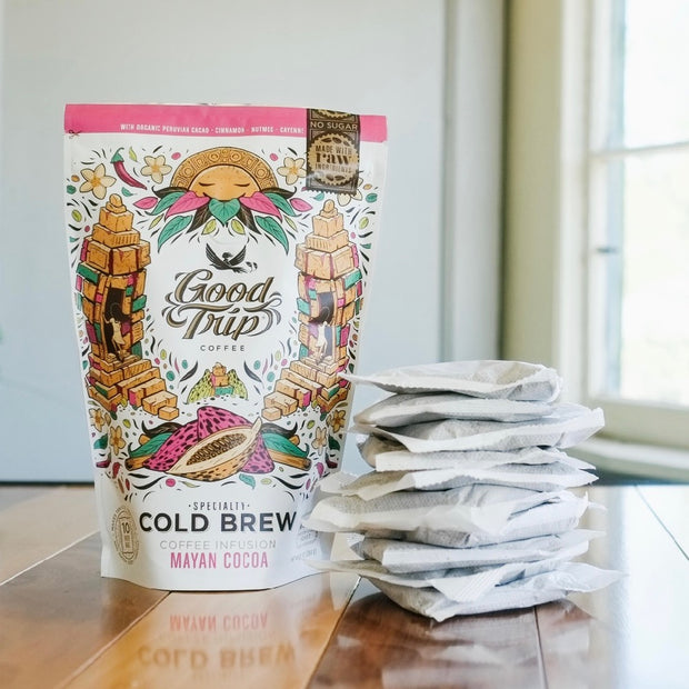 bag of good trip coffee mayan cocoa cold brew sitting on table next to stack of compostable ready-to-steep brew bags
