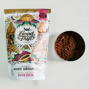 bag of good trip coffee mayan cocoa mixed grounds sitting on white table next to ingredients