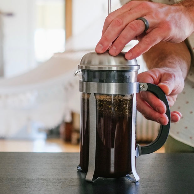 man brewing mixed grounds in french press on dark wood table