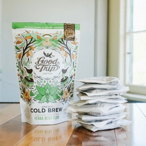 bag of good trip coffee yerba mint flow cold brew sitting on table next to stack of compostable ready-to-steep brew bags