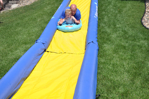 The Turbo Chute Water Slide Backyard Package by Rave Sports with people sliding down it