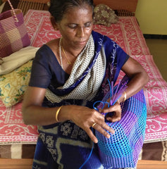 Rajathi Seniyappan handweaving a basket in her home