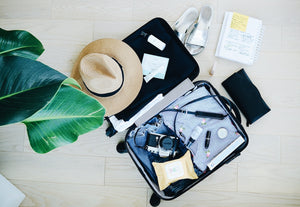 Flat lay of open suit case being packed for a summer holiday | Sustainable travel ZERRIN