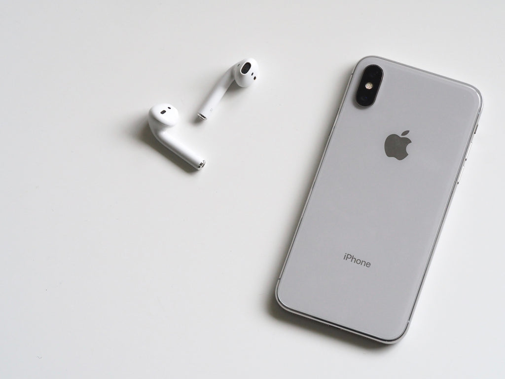 Image of iPhone and Airpods to accompany article on sustainable fashion podcasts on ZERRIN