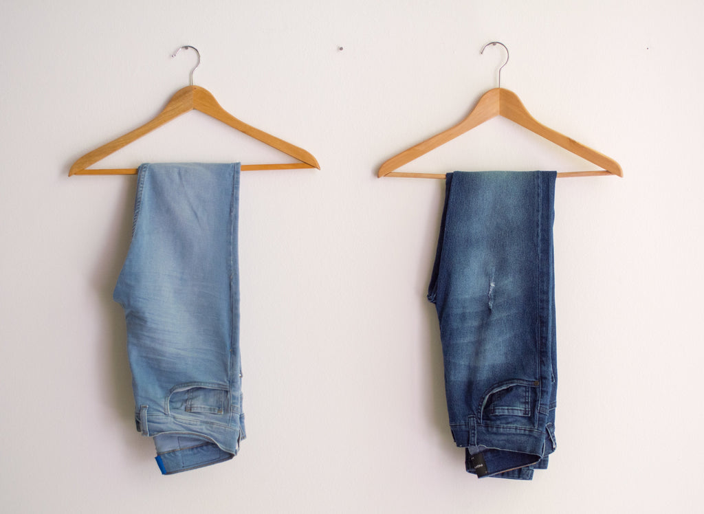 Image of jeans on hangers to accompany article on sustainable fashion on ZERRIN