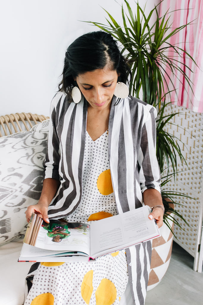 Sustainable fashion brand owner Rakhee Shah of Maisha Concept flicks through a book during ZERRIN interview