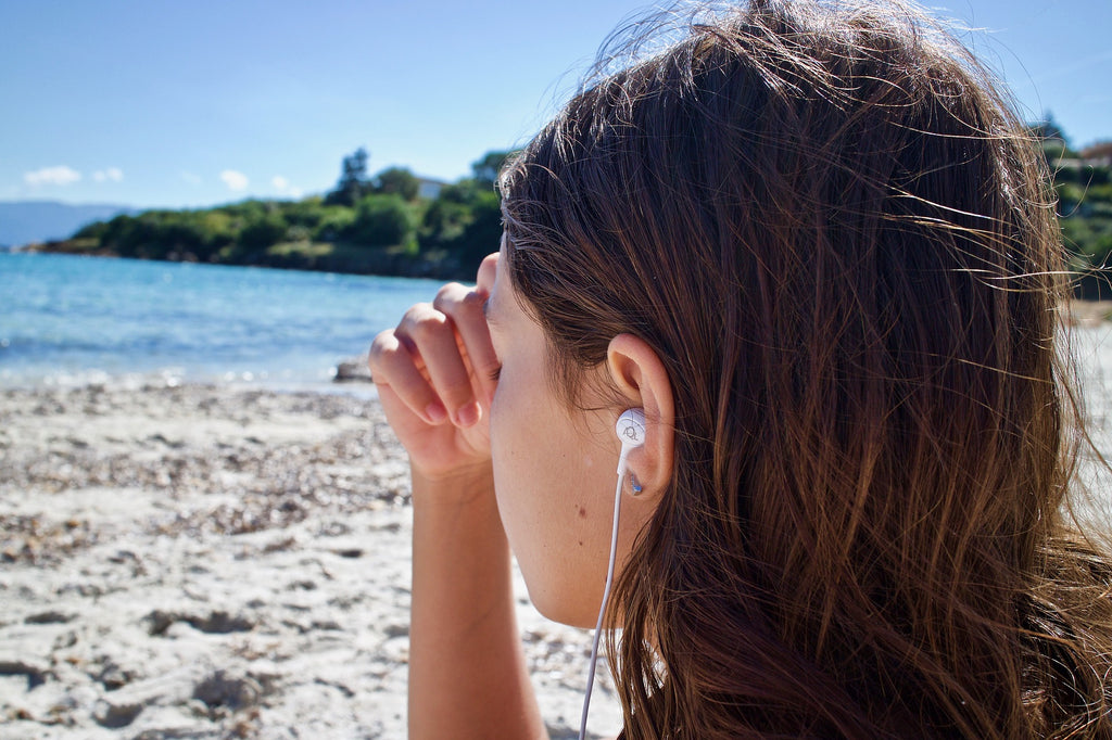 Image of women with earphones to accompany article on sustainable fashion podcasts on ZERRIN