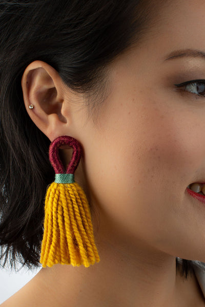 Model wears Talee Aru loop tassel earrings in wine and mustard available on sustainable fashion store ZERRIN