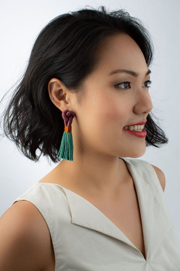 Model wears Talee tassel Hati earrings in plum and rainforest colour, available on sustainable fashion store ZERRIN