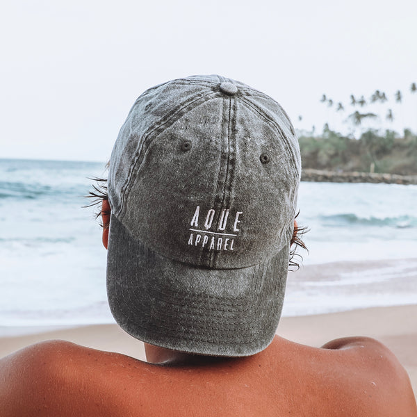 Gorra Aqüe Apparel negra efecto lavado, ajustable. Black Aqüe Apparel cap washed effect fabric, adjustable strap-back closure. 6 Panel Dad Cap. 100% cotton.