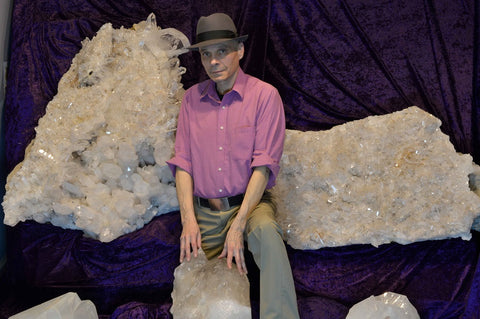 Mineral and crystal gallery, Jesse Martinez, manager standing by large crystals