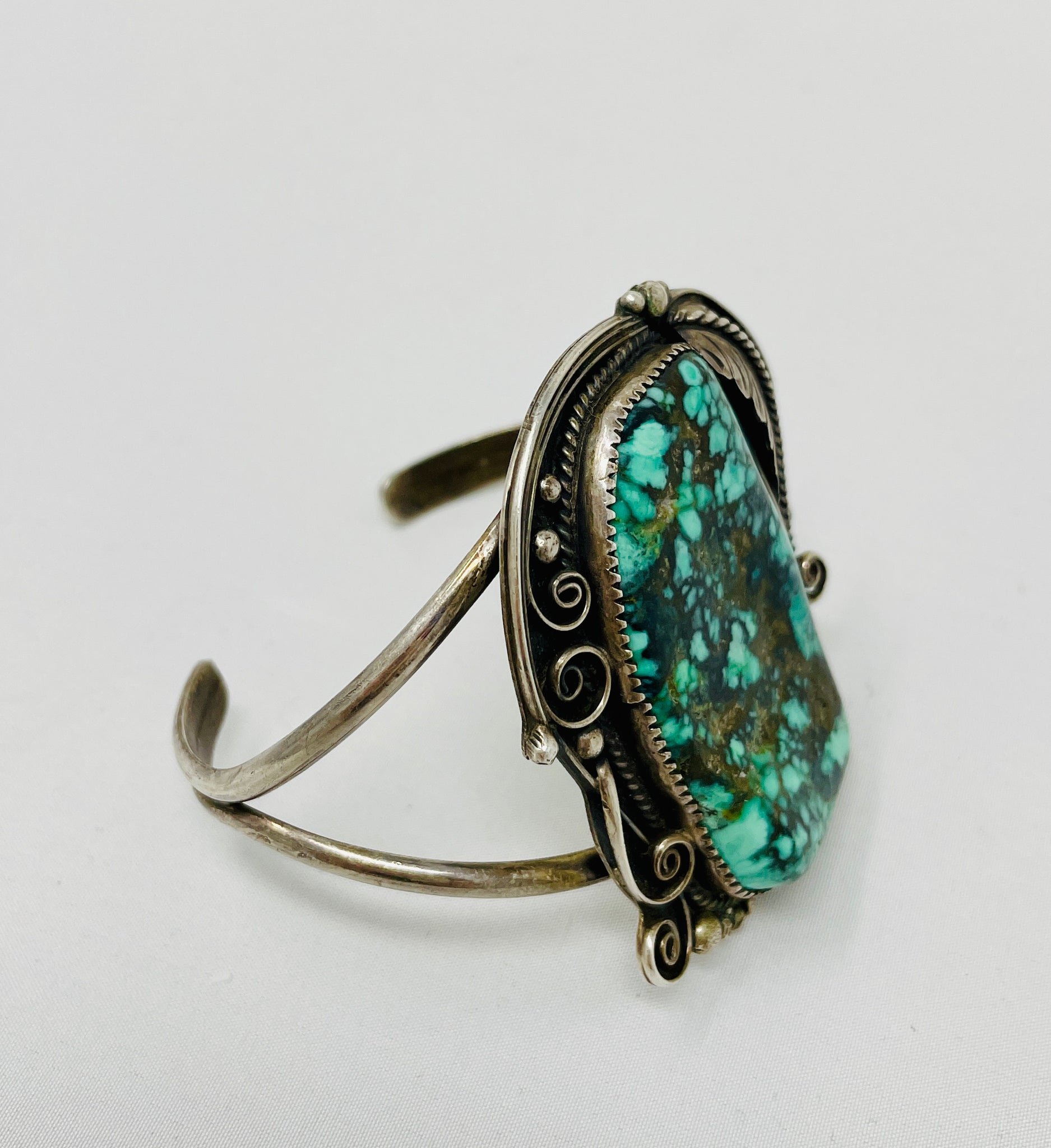 Heavy Navajo Cuff with Raindrops and Stampwork on Leaves Surrounding Stunning Turquoise Stone
