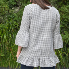Female showing the back of the Celia top in blue and white checked fabric