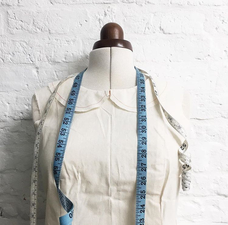 Mannequin dressed in a toile and measuring tapes