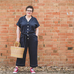 Female wearing Cressida Jumpsuit Sewing Pattern standing in front of a  brick wall