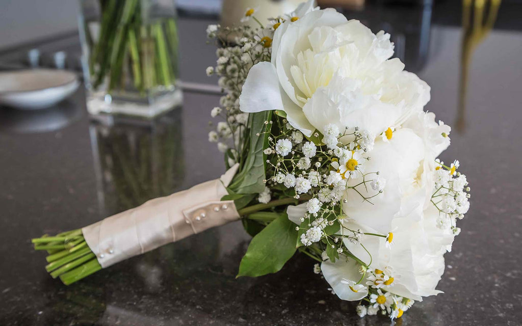 a bridal bouquet of white roses with gypsophila and matricaria